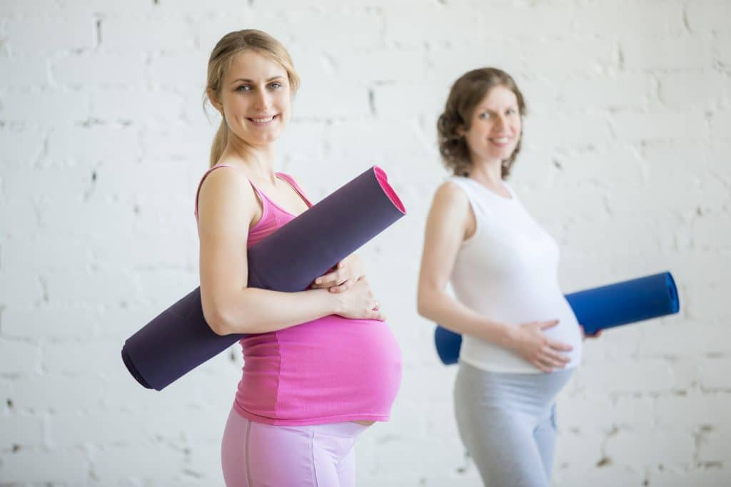 Two pregnant women with exercise mats