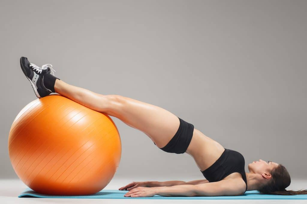 Young woman with a pilates ball doing pelvic floor exercise